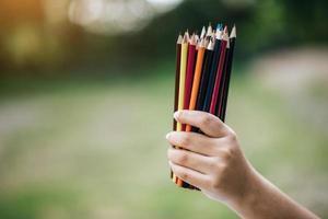 bunte Stifte in der Hand auf grünem Hintergrund