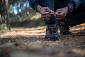 Der junge Wanderer bindet seine Schnürsenkel, während er im Wald wandert foto