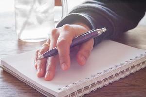 Hand mit einem lila Stift auf einem Notizbuch