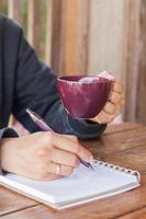 Person, die eine lila Kaffeetasse hält und schreibt