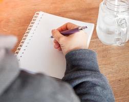 Person, die in ein Notizbuch mit einem Glas Wasser schreibt