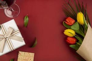 Draufsicht eines Blumenstraußes mit Wein und einem Geschenk auf einem roten Hintergrund
