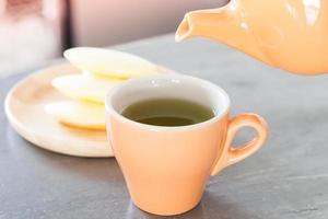 grüner Tee in einer orangefarbenen Tasse