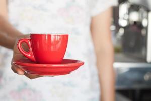 Barista hält eine rote Kaffeetasse