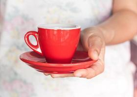 Person, die eine rote Kaffeetasse hält