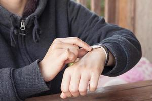 Person, die die Zeit auf einer Armbanduhr überprüft