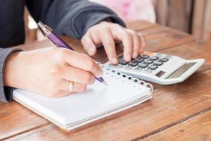 Person, die Notizen schreibt und Berechnungen vornimmt