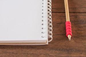 Nahaufnahme eines roten Bleistifts und eines Notizbuchs