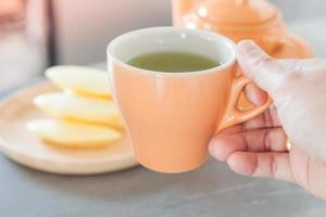 Hand hält eine Tasse Tee
