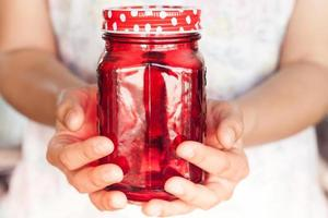 Person, die ein rotes Glas hält