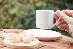 Hand hält eine Kaffeetasse
