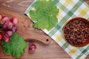 Draufsicht auf eine Schüssel Rosinen und Trauben mit einem Tuch foto