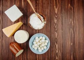 Draufsicht von verschiedenen Käsesorten auf einem hölzernen Hintergrund