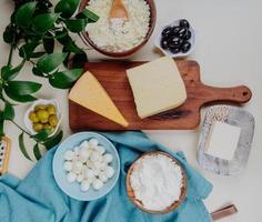 Draufsicht auf verschiedene Käsesorten auf einem Schneidebrett und Stoff