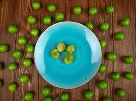 Draufsicht einer blauen Platte mit grünen Pflaumen auf einem hölzernen Hintergrund foto
