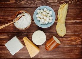 Draufsicht von verschiedenen Käsesorten auf einem rustikalen hölzernen Hintergrund