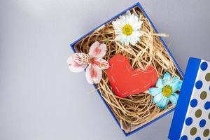 Draufsicht auf eine Schachtel mit Blumen und ein Filzherz foto