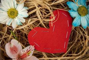 Draufsicht der bunten Gänseblümchenblumen und der rosa Alstroemeria mit einem Herzen, das vom roten Farbpapier auf Strohhintergrund gemacht wird