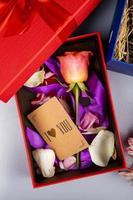 Draufsicht der Farbfarbe Rosenblume mit lila Band und kleiner brauner Papierkarte in einer roten Geschenkbox auf weißem Hintergrund