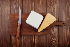 Draufsicht von Käsestücken mit einem Küchenmesser auf einem hölzernen Schneidebrett
