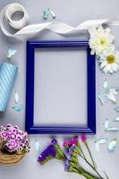 Draufsicht auf einen leeren Bilderrahmen mit Blumen und Bändern foto