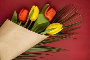 Draufsicht auf einen Strauß roter und gelber Tulpen in Kraftpapier
