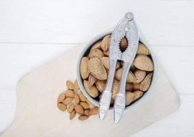 Draufsicht auf eine Schüssel Mandeln mit einem Nussknacker foto