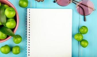 Draufsicht auf ein Skizzenbuch mit Sonnenbrille und sauren Pflaumen foto