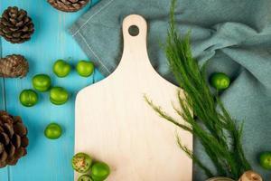 Draufsicht auf ein Holzbrett mit grünen Pflaumen und Tannenzapfen foto