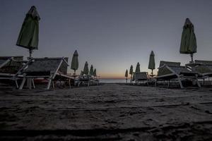 Liegestühle mit Sonnenschirmen am Strand bei Sonnenuntergang