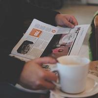 Person, die liest, während sie weißen Keramikbecher hält