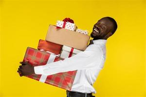 Mann hält einen Stapel Geschenke foto