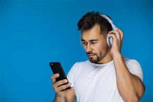 Europäischer Mann beobachtet etwas auf seinem Telefon und hört Kopfhörer foto