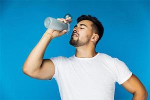 Mann trinkt aus Wasserflasche