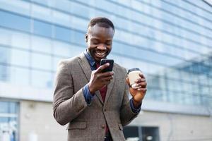 Mann mit einem Kaffee auf seinem Telefon lesen foto