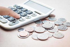Nahaufnahme einer Hand auf einem Taschenrechner mit Münzen