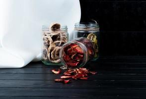 Gläser mit getrockneten Früchten auf einer schwarzen Holzoberfläche