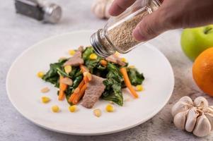 Hand Sesam über einen Teller mit Essen gießen