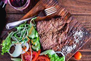 Nahaufnahme von Steak und auf einem hölzernen Schneidebrett foto