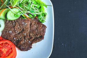 Steak mit Salat auf einem Teller foto