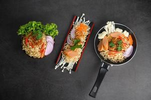 drei Gerichte von würzigen Nudeln auf grauem Hintergrund