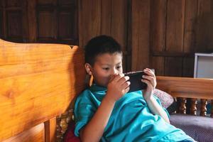 Junge spielt am Telefon foto