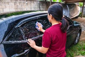 Frau, die ein Autofenster wäscht foto
