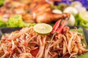 thailändischer Papayasalat, umgeben von Gemüse und Hühnchen foto