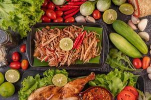 thailändischer Papayasalat, umgeben von Gemüse und Hühnchen