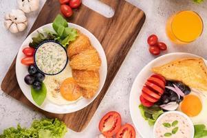 Croissant, Spiegelei, Salatdressing, schwarze Trauben und Tomaten foto