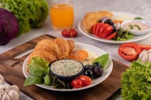 Croissant, Spiegelei, Salatdressing, schwarze Trauben und Tomaten