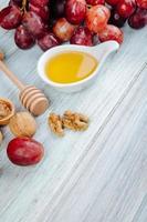 Honig mit einem hölzernen Honiglöffel und Trauben foto