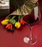Glas Rotwein mit einem Blumenstrauß foto
