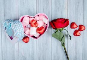 Draufsicht auf Valentinsbonbons und eine Rose